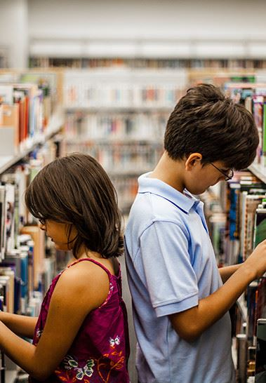 Kids searching for a book at the library