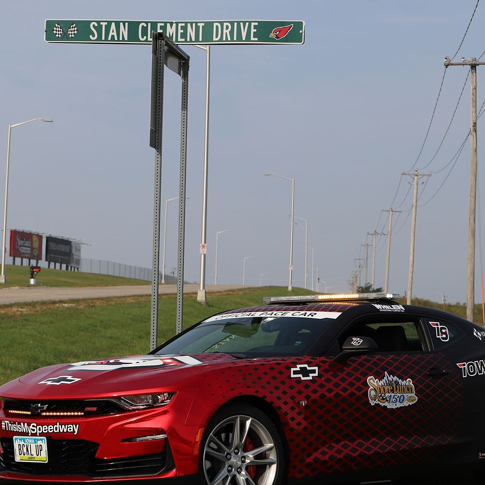 Newly named Stan Clement Drive sign with Iowa Speedway pace car parked in front of it.