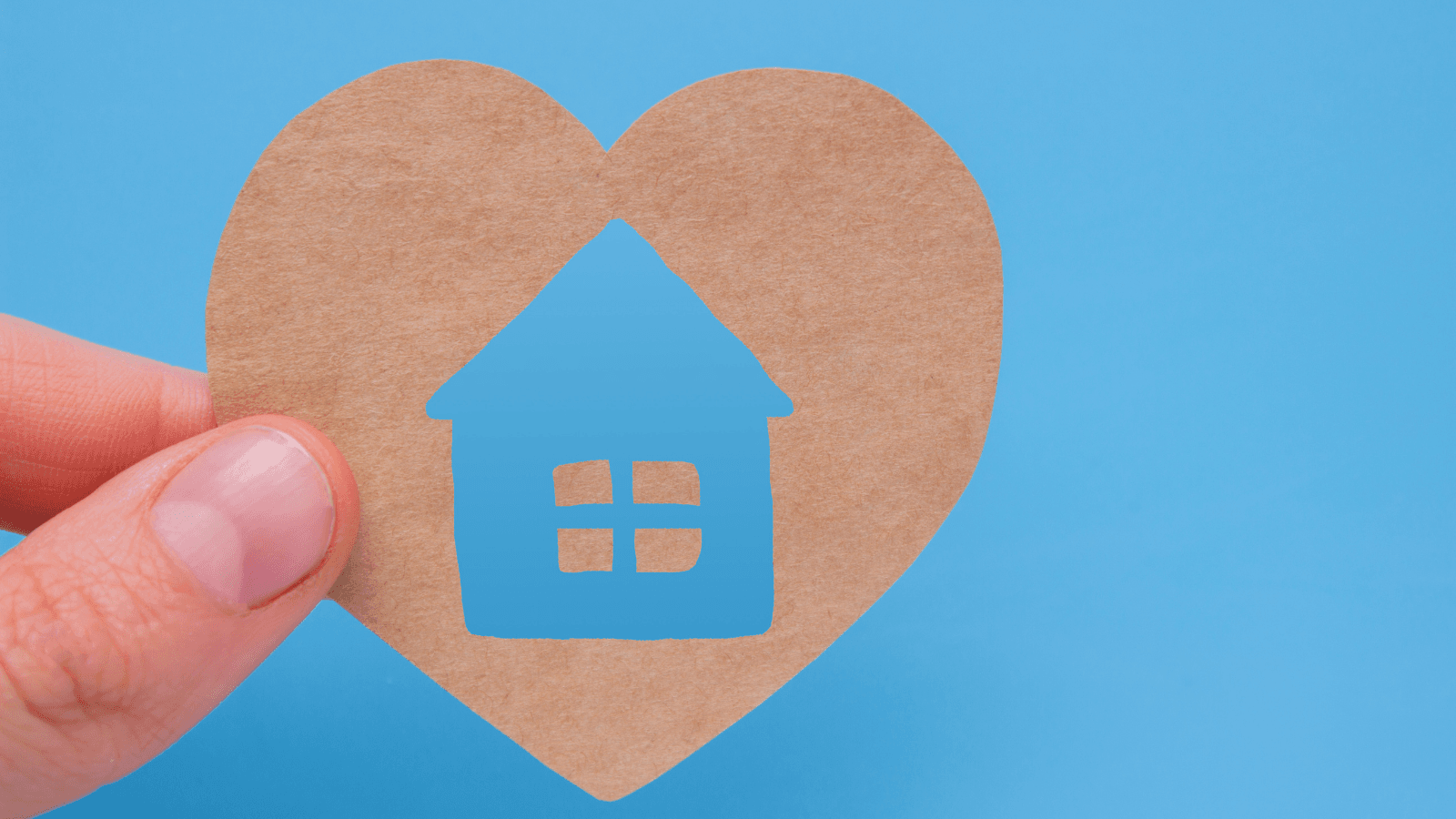 A heart with a house shape cutout being held by a hand against a blue background.